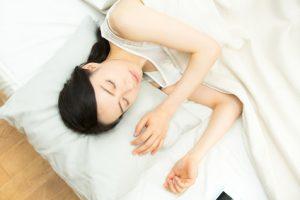 女性・ベッド・スマートフォン